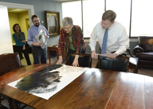 "Katherine Calos unrolls the signed ""Lincoln"" movie poster on Paul Levengood's desk"