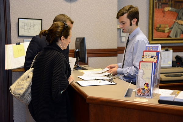 Photograph of Tony helping patrons register in the VHS library.