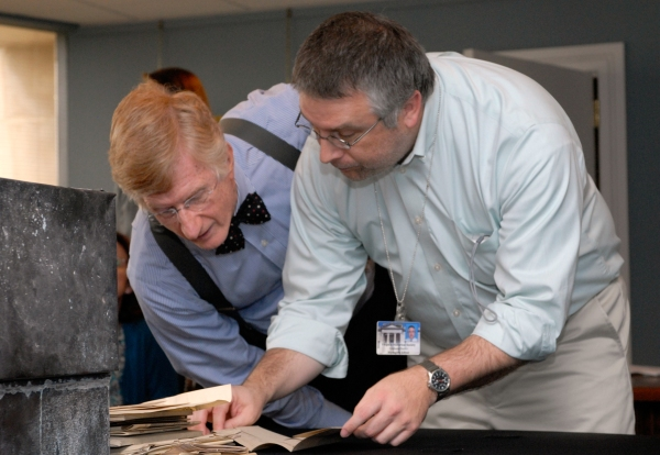 Photograph of Graham Dozier and Nelson Lankford looking at documents from the time capsule.