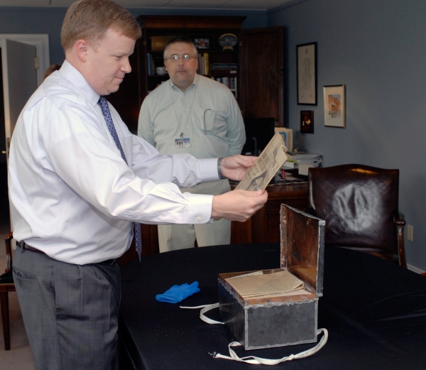 Photograph of Graham Dozier and Paul Levengood looking at documents from the time capsule.