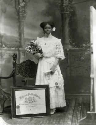 "Photograph, "" Leonie Helen Holmes,"" 1909. In this photograph, Leonie Helen Holmes holds a diploma while a second, framed diploma sits at her feet. The diploma on the floor is her diploma from Richmond Colored Normal and High School; the one in her hand is probably a diploma from a six- to eight-week summer ""normal""—a special program designed to train teachers. Summer normals were instituted around 1906 as part of the state's efforts to reform public schools by establishing standards for teachers. (VHS accession number: 2003.298.29 a)"