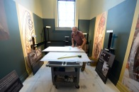 """Exhibit Designer, Bryan Condra, installing the """"Charles Hoffbauer: Painter of Historical Murals"""" exhibition in the William Goode Beville and Charlotte Beville Hale Gallery."""