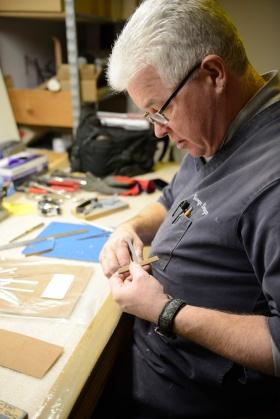A mount-maker carefully prepares a custom-made mount.